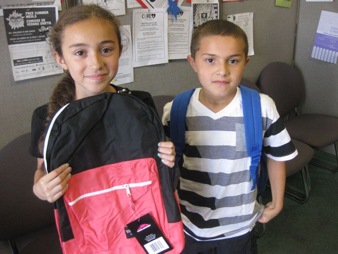 Two students with the backpacks of school supplies supplied by Together We Cope.