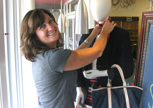 Woman dresses a mannequin at Nu2u Resale Shop in Tinley Park to kick off the Back to School Program at Together We Cope that provides student school supplies for needy children.