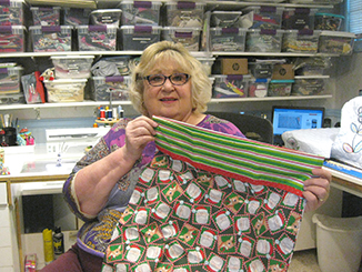 Karen Persing sitting at a sewing machine and holding up some Christmasy print pillowcase material
